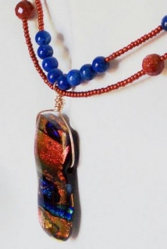 Photo of dichroic glass bead used as a focal bead in a pendant design