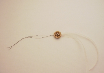 Thread through bead holes and pull ribbon through the bead