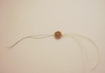 Thread through bead holes and pull ribbon through the bead